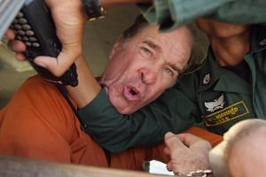 Australian filmmaker James Ricketson (centre), is blocked by a Cambodian police officer in a police van while leaving the Municipal Court in Phnom Penh, Cambodia, on Aug 31, 2018.