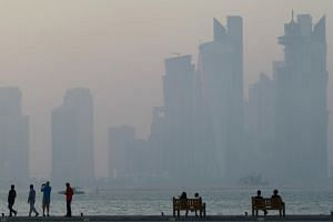 People sit on the corniche in Doha on June 15, 2017. A senior Saudi official appeared to confirm reports that the kingdom is considering digging a canal to separate the Qatari peninsula from the mainland and turn it into an island.