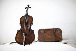 The violin played by bandmaster Wallace Hartley during the final moments before the sinking of the Titanic, with a leather carrying case initialed W H H, at a conservation studio in Lurgan, Northern Ireland.