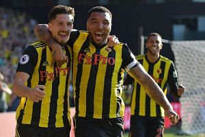Watford defender Craig Cathcart (far left) and striker Troy Deeney make a happy pair after the former scored the winner against Tottenham in their league match. Deeney had netted the equaliser at Vicarage Road on Sunday.