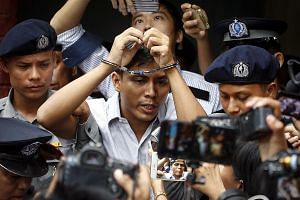Reuters journalist Kyaw Soe Oo is escorted out of the Insein township court in Yangon after the verdict. He and fellow Reuters journalist Wa Lone say they were framed for the crime. The two men were reportedly invited to dinner by the police, given s