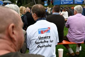 A supporter of Germany's Alternative for Germany (AfD) party wearing a t-shirt that reads 'Our language is German' attends the traditional Gillamoos festival in Abensberg, Germany, on Sept 3, 2018.