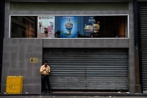 A man eats a dessert next to closed restaurant of the food chain McDonald's, in Caracas on Sept 2, 2018.