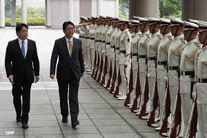 Japan's Prime Minister Shinzo Abe (second, left) and Defence Minister Itsunori Onodera (left) review an honour guard during Mr Abe's visit to the Defence Ministry to meet with senior officials in Tokyo, on Sept 3, 2018.