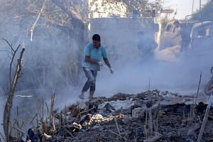 Syrians use dirt to put out a fire at the scene of a reported air strike in Jisr al-Shughur district, in Idlib province.