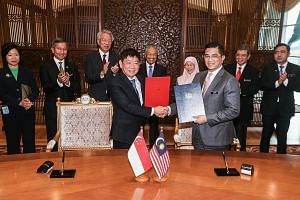 Singapore's Coordinating Minister for Infrastructure and Minister for Transport Khaw Boon Wan and Malaysia's Economic Affairs Minister Mohamed Azmin Ali at the signing ceremony at the Malaysian Prime Minister's Office in Putrajaya yesterday. With the