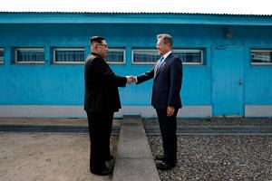 North Korea's leader Kim Jong Un and South Korea's President Moon Jae-in greet each other at the Military Demarcation Line that divides their countries at the truce village of Panmunjom, on April 27, 2018.
