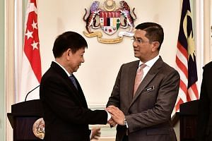 Transport Minister Khaw Boon Wan and Malaysian Economic Affairs Minister Mohamed Azmin Ali at a news conference on Wednesday after the high-speed rail signing ceremony in Putrajaya. The official joint statement after the agreement to pause the projec