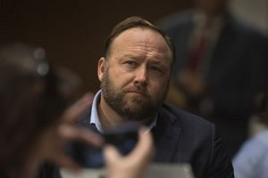Alex Jones looks on as the leaders of Twitter and Facebook testify at a hearing of the Senate Intelligence Committee.