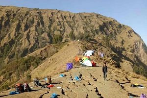 People camping out on the ridge of Mount Rinjani, following landslides triggered by the Lombok earthquake, on July 30, 2018.