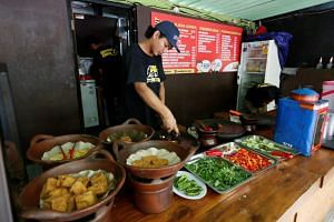 A cook at a restaurant which offers free meals for people who can show they have recently changed US dollars for Indonesian rupiah at their outlet in Jakarta, Indonesia, on Sept 7, 2018.