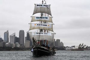 A ship, the Southern Swan, sails in Sydney Harbour in front of the Opera House with environmentalists on board, on Sept 8, 2018.