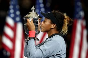 Naomi Osaka of Japan poses with the championship trophy.