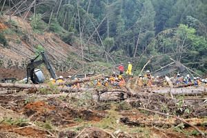Officials search for missing people in the devastated city of Atsuma on Sept 9, 2018, after a 6.6-magnitude earthquake hit the northern Japanese island of Hokkaido on Sept 6, 2018.