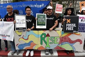 Environmental activists shout slogans during a demonstration in front of the United Nations building, where experts from across the planet locked in key talks aimed at breathing life into the Paris Agreement on climate change, in Bangkok on Sept 8, 2