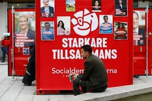 A man sits next to Sweden's Social Democrats party election campaign booth in the Rinkeby neighbourhood in Stockholm, Sweden, on Sept 7, 2018.