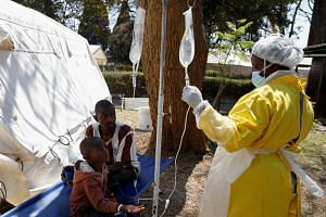 Patients await treatment at a makeshift cholera clinic in Harare, Zimbabwe, on Sept 11, 2018. The latest cholera outbreak came after burst sewers contaminated water in boreholes and open wells used by residents.