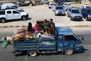 Displaced Syrians who fled from regime raids ride in a truck with their belongings arrive near a camp in Kafr Lusin, near the border with Turkey, in the northern part of Syria's rebel-held Idlib province, on Sept 9, 2018.