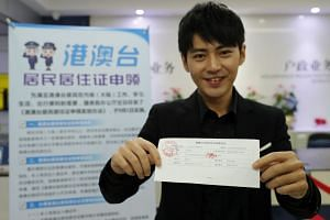 Taiwanese citizen Sun Chih-wei with a registration receipt after submitting his application for an identity card for Taiwanese, Macau, and Hong Kong residents on mainland China at a police station in Guangzhou, China, on Sept 1, 2018.