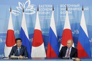 Japanese Prime Minister Shinzo Abe (left) and Russian President Vladimir Putin deliver their statements at a joint press conference following their talks in Vladivostok, Russia, on Sept 10, 2018.
