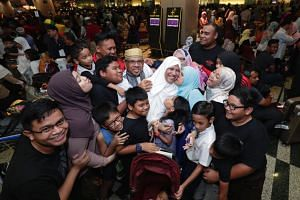 Returning Haj pilgrims Abdullah Ahmad (centre, in gold songkok) and his wife Safiah Ahmad (centre, in white tudung) receive a group hug from family members at Changi Airport Terminal 3, on Sept 12, 2018.