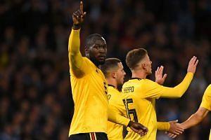 Belgium's striker Romelu Lukaku (left) celebrates with teammates after scoring.