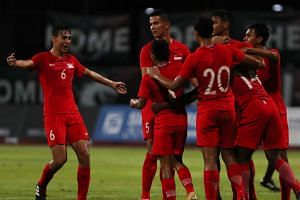 Lions debutant Jacob Mahler (left) joining his team-mates in celebrating Hariss Harun's goal. The midfielder's (No. 14) goal set Singapore on their way to a 2-0 win at the Bishan Stadium, their first under Fandi Ahmad.