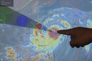 A weather forecaster points out the predicted tract of Typhoon Mangkhut in the town of Aparri, Cagayan province, Philippines, on Sept 14, 2018.