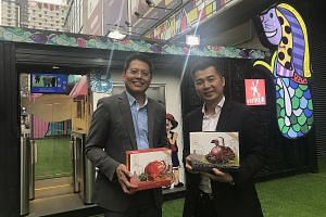 VeriTAG chief executive Jason Lim (left) at the firm's first unmanned minimart in Chengdu, which showcases food from up to 20 Singapore brands, including frozen crab dishes from House of Seafood. With him is the Singapore restaurant chain's chief exe