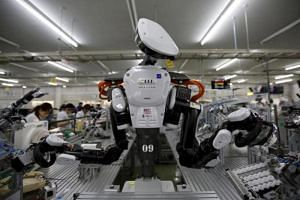 A humanoid robot works side by side with employees in the assembly line at a factory of Glory Ltd, a manufacturer of automatic change dispensers, in Kazo, north of Tokyo, Japan.