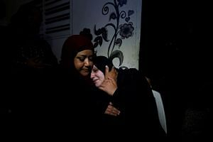 The mother of Shadi Abdel Aal is comforted as she mourns during his funeral.