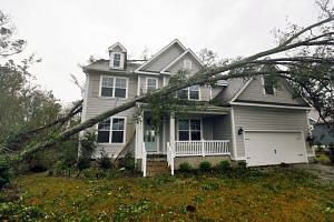 A tree rests on a newly constructed house after Hurricane Florence struck in Belville, North Carolina, on Sept 15, 2018.