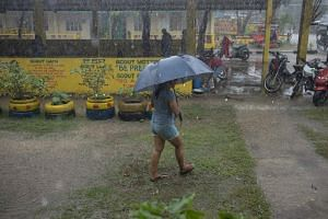 A woman holding an umbrella during heavy rainfall outside a temporary evacuation centre ahead of Typhoon Mangkhut's arrival in Tuguegarao, the Philippines, on Sept 14, 2018.