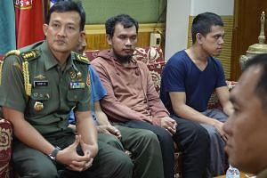 An Indonesian military officer (left) sits with two of three recovered Indonesian nationals at a military camp in Zamboanga City, southern Philippines, on Sept 16, 2018.