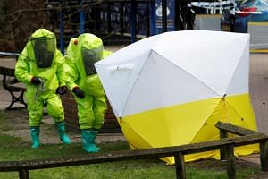 The forensic tent, covering the bench where Sergei Skripal and his daughter Yulia were found, is repositioned by officials in protective suits in the centre of Salisbury, Britain, on March 8, 2018.