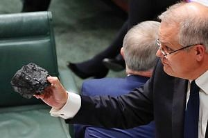 Mr Scott Morrison holding up coal in Parliament last year to show that Australia should not be afraid of the carbon-emitting resource. Now prime minister, he has avoided committing to a new policy to curb emissions.