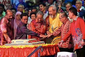 Malaysian Prime Minister Mahathir Mohamad, flanked by Sabah Governor Juhar Mahiruddin (in yellow) and Sabah Chief Minister Mohamad Shafie Apdal, cutting a cake with Sarawak Deputy Chief Minister Amar Douglas Uggah Embas (red batik) during the Malaysia Day