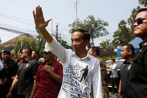 Indonesian President Joko Widodo waves to supporters after registering himself and his running mate Islamic cleric Ma'ruf Amin (not pictured) for the 2019 presidential election, in Jakarta, Indonesia on Aug 10, 2018.