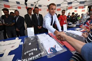 French President Emmanuel Macron shakes hands with a visitor next to items for sale at the Elysee Palace in Paris, on Sept 15, 2018.