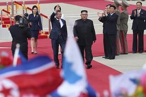 South Korean president Moon Jae-in (waving in front) and North Korean leader Kim Jong Un walk the red carpet during a welcome ceremoney at the Sunan International Airport in Pyongyang, North Korea, on Sept 18, 2018.