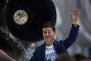 Japanese billionaire Yusaku Maezawa speaks near a Falcon 9 rocket at the SpaceX headquarters and rocket factory on Sept 17, 2018 in Hawthorne, California.