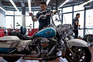 Workers at a Harley-Davidson dealership in Shanghai. From American motorcycles and bourbon to Chinese machines and parts, the world's two largest economies have exchanged punitive tariffs that slice through a wide swathe of products.