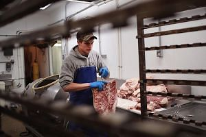 A worker at Elma Locker & Grocery in Iowa, which is the top US state for pork exports. Pork producers in the state are bracing themselves for the impact of a trade war with China.
