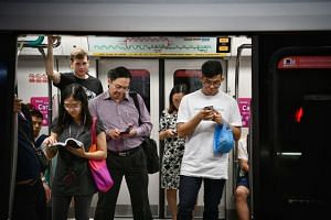 File photo showing commuters looking at phones on the MRT. The Select Committee said that any new laws must respect personal and private communications and avoid harming public interest.
