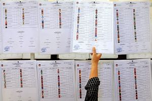 A woman scrutinises a list of Regional Representatives Council candidates at the General Elections Commission.