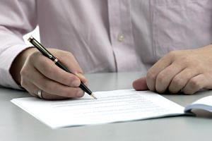 A posed photo of a man signing a document. The newly launched Professional Deputies and Donees scheme allows people to pay registered professionals to act on their behalf should they become mentally incapacitated in the future.