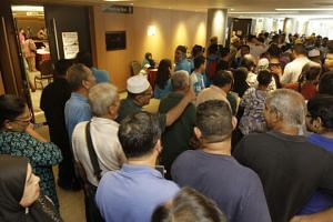 Long lines of people at the Spice Centre, the venue for the Bayan Baru PKR division election, as members waiting to cast their votes are delayed by a problem with the electronic system.