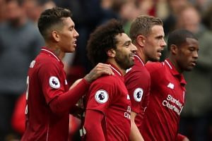 Salah celebrates scoring Liverpool's third goal with teammates.