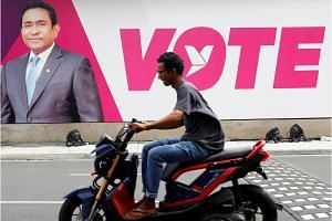 A man rides a motorcycle past an image of Maldives President Abdulla Yameen ahead of the presidential election in Male, on Sept 19, 2018.