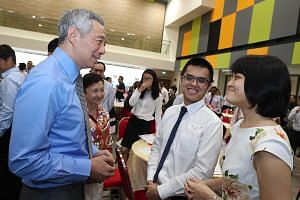 Prime Minister Lee Hsien Loong interacting with two new Singapore citizens - Mr Wong Songhan and his wife, Ms Pang Sheau Shiuh - at yesterday's citizenship ceremony in Teck Ghee Community Club. Mr Lee urged the 150 new citizens to be active citizens